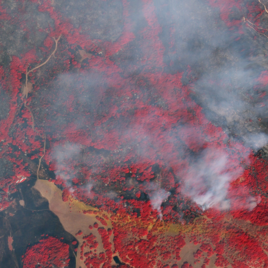 A false-color composite including near-infrared light reveals burns scars (dark gray) and unburned woodland (bright red) under the smoke. Flame retardant is red in true color, and orange in false-color.