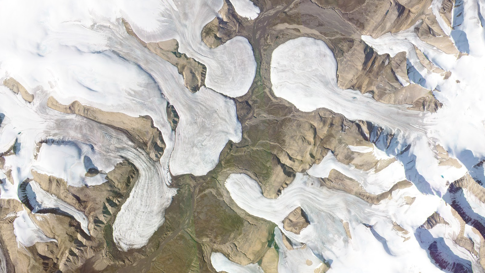 Glaciers spill into a barren valley on Axel Heiberg Island, Canada. PlanetScope image collected on August 15, 2019. © 2019, Planet Labs Inc. All Rights Reserved.