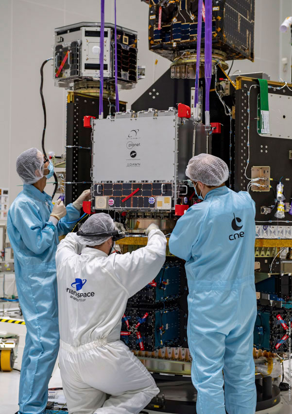 Technicians performing payload integration of the D-Orbit ION CubeSat deployer carrying 12 Flock 4v SuperDoves, with Planet's logo clearly visible. The remaining 14 SuperDove satellites are housed inside the blue and black ISL QuadPack deployers visible on the lower deck. Image provided by Arianespace.